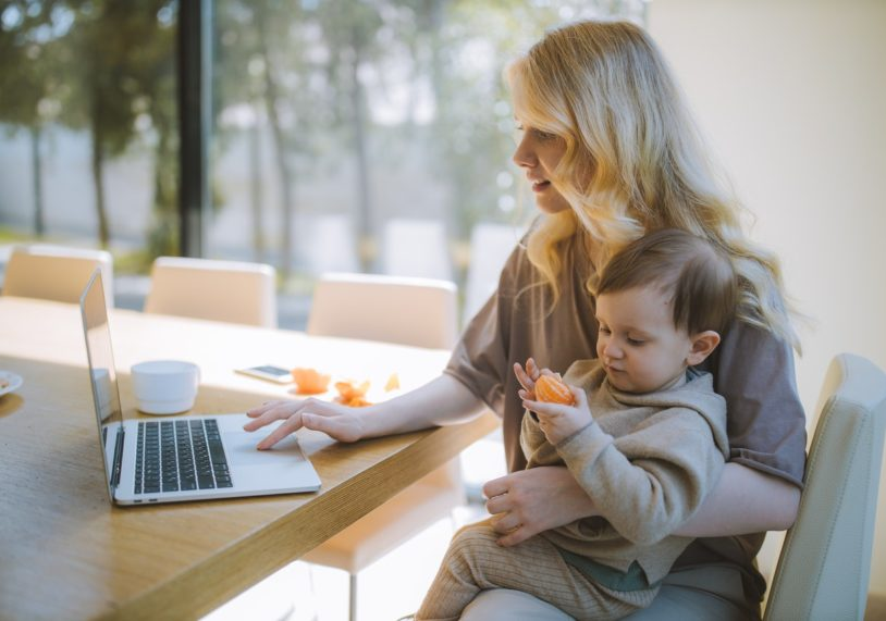 Mom using laptop and holding baby